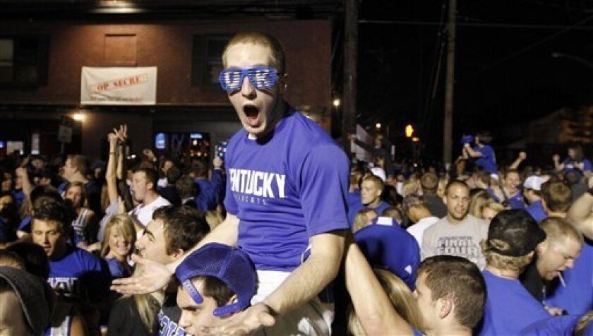Ethen Farley yells with other Kentucky fans as they celebrate Kentucky's 69-61 win over Louisville in an NCAA Final Four semifinal college basketball tournament game, Saturday, March 31, 2012, in Lexington, Ky. (AP Photo/The Courier-Journal, James Crisp) NO SALES; MAGS OUT; NO ARCHIVE; MANDATORY CR