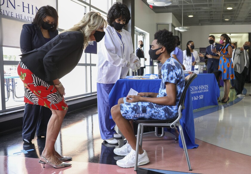 First Lady Jill Biden, in a black mask, leans down to speak to a masked young man seated near health workers