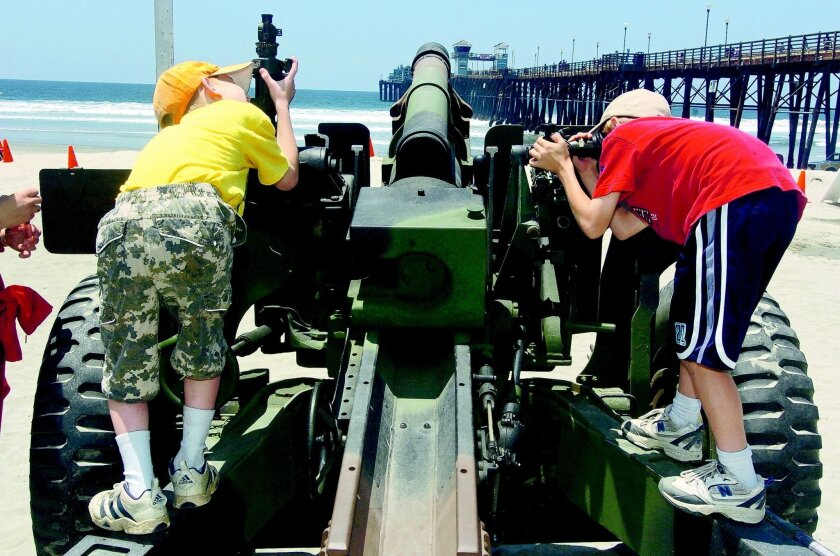 Toby Wiest, 8, left, and his brother Andrew Wiest, 10, both look through the sites of a 105 mm Howitzer, which was used from World War II to Vietnam, during the Operation Appreciation held in Oceanside on Saturday. Photo Hayne Palmour IV