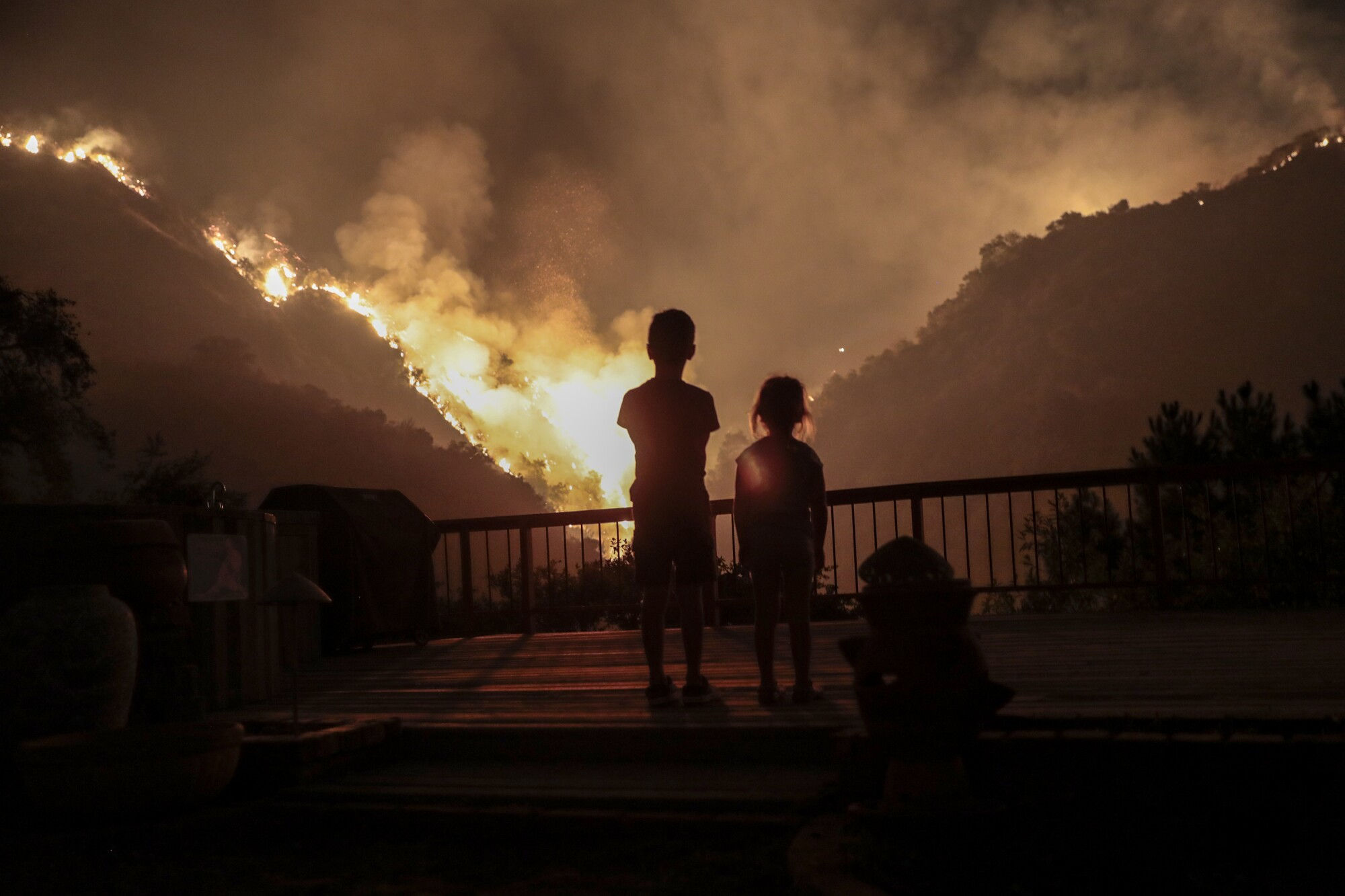Castle Snider, 8, and Iris Snider, 4, look on as the Bobcat fire burns near homes on Oakglade Drive, Monrovia.