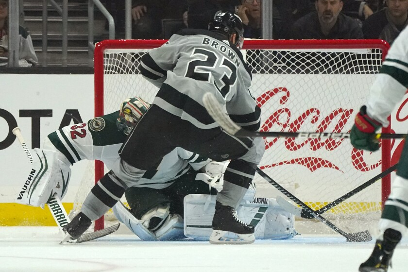 Kings forward Dustin Brown scores on Minnesota Wild goaltender Alex Stalock during the third period of the Kings' 7-3 win Saturday.