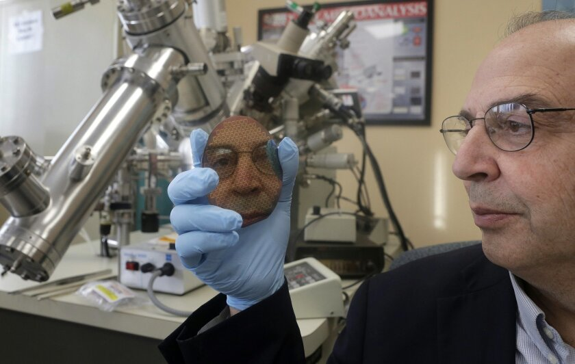 In this Tuesday, Jan. 26, 2016 photo University of Rhode Island engineering professor Otto Gregory, right, is reflected in a silicon wafer, center, that contains sensors to detect explosives, in front of a thin film surface analyzer, behind, in a laboratory on the school's campus, in South Kingstow