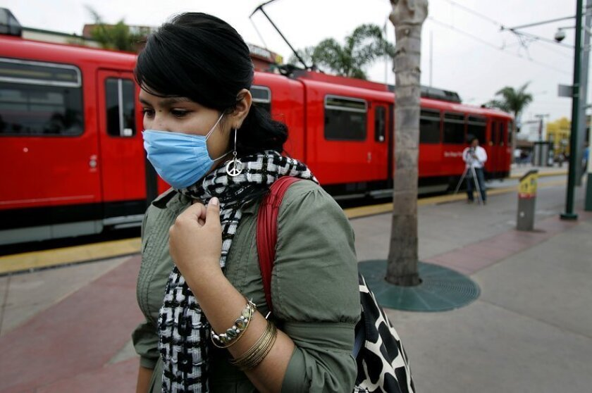 Rachel Ontiveros, 18, of San Diego, wears a mask at the San Ysidro border crossing as she returns from visiting family in Tijuana, Mexico. She wore the mask for her protection from possible swine flu infection.