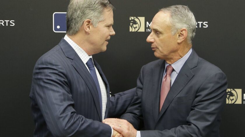 MGM Resorts CEO James Murren, left, and MLB Commissioner Rob Manfred shake hands after a news conference at MLB headquarters in New York on Tuesday.