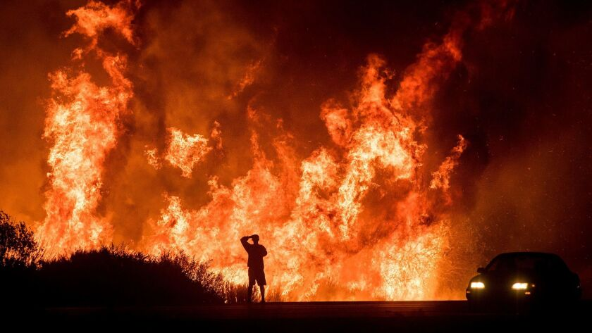 A motorist on Highway 101 watches flames from the Thomas fire leap above the roadway north of Ventura, Calif. on Dec. 6, 2017.