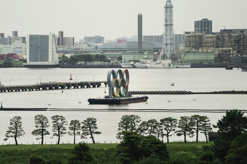 A large sculpture of the five interlocked Olympic rings on a platform in a harbor in Tokyo