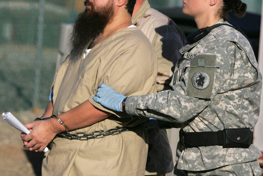 FILE - In this Dec. 6, 2006 file photo, reviewed by a U.S. Dept of Defense official, a shackled detainee is transported by a female guard, front, and male guard, behind, away from his annual Administrative Review Board hearing with U.S. officials, at Camp Delta detention center, Guantanamo Bay U.S.