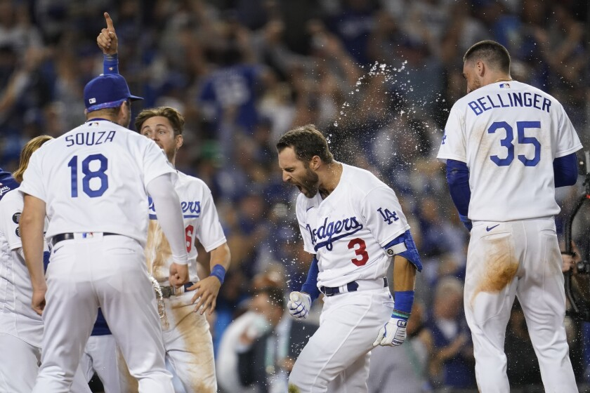 The Los Angeles Dodgers celebrate with Chris Taylor (3) after he hit a home run during the ninth inning to win a National League Wild Card playoff baseball game 3-1 over the St. Louis Cardinals Wednesday, Oct. 6, 2021, in Los Angeles. Cody Bellinger (35) also scored. (AP Photo/Marcio Jose Sanchez)
