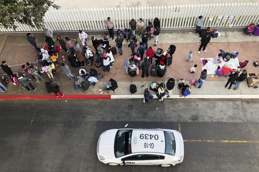 In this Nov. 10, 2019, photo, migrants gather at the U.S.-Mexico border in Tijuana, Mexico, to hear names called from a waiting list to claim asylum in the U.S. (AP Photo/Elliot Spagat)