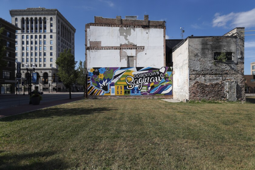 Buildings from different eras of the city's history surround an empty lot in downtown Saginaw, Mich., Monday, June 29, 2020. President Donald Trump won Saginaw county by just over 1,000 votes in 2016, capitalizing on the rusting industrial city's frustrations and its dislike of Democrat Hillary Clinton. (AP Photo/Charles Rex Arbogast)