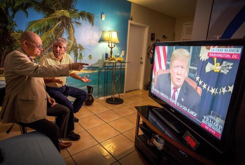 Varias personas ven al presidente de los Estados Unidos, Donald J. Trump, en la televisión, hoy, desde su casa, en Miami, Florida (EE.UU.). La disputa por el muro en la frontera sur de Estados Unidos saltó hoy al horario de máxima audiencia en ese país, con sendos discursos del presidente estadounidense, Donald Trump, y los líderes demócratas del Congreso, que no logran acercar posiciones para reabrir la Administración. EFE/Archivo