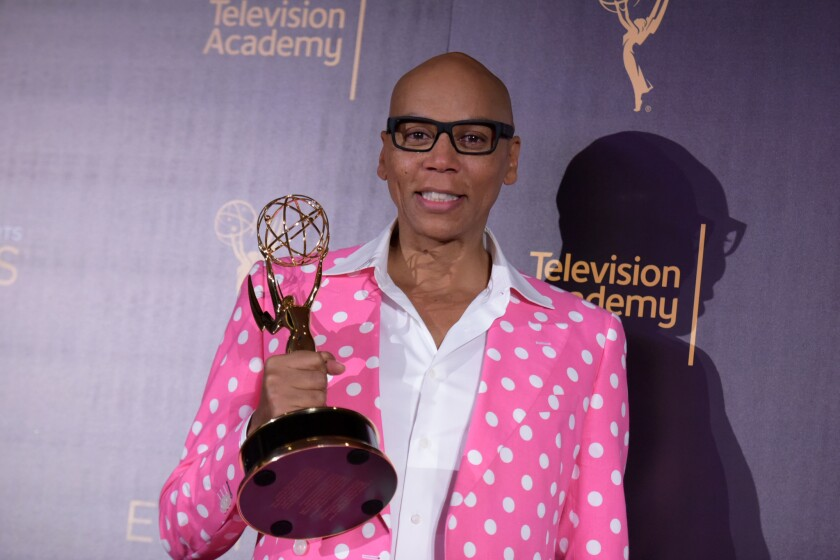 """RuPaul Charles poses in the press room with his award for outstanding host for a reality or reality-competition program for """"RuPaul's Drag Race"""" on Sunday."""