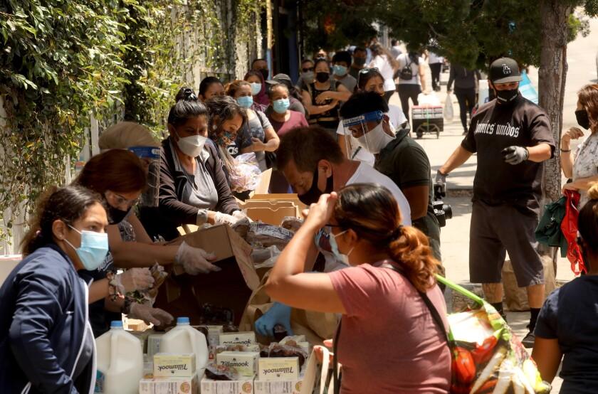 Members of Homies Unidos put food in bags for needy families in Los Angeles' Koreatown.