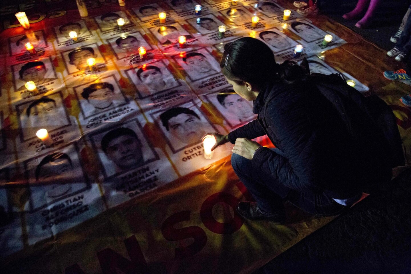 A woman places a candle on photos of the missing students during a protest against the disappearance of 43 students from the Isidro Burgos rural teachers college, in Mexico City, Wednesday, Oct. 22, 2014. Tens of thousands marched in Mexico City's main avenue demanding the return of the missing stu