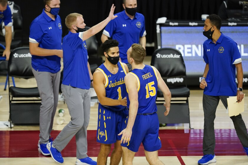 South Dakota State guard Noah Freidel (15) celebrates with teammate Matt Mims (1) at the end of an NCAA college basketball game against Iowa State, Wednesday, Dec. 2, 2020, in Ames, Iowa. South Dakota State won 71-68. (AP Photo/Charlie Neibergall)