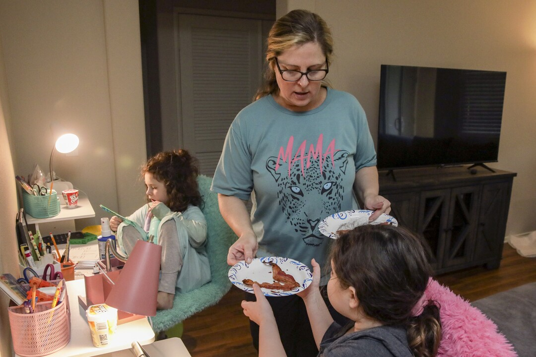 Alison Goldberg, 43, gives lunch to Savannah Singer, foreground, and Madelynn Singer while attending online school.