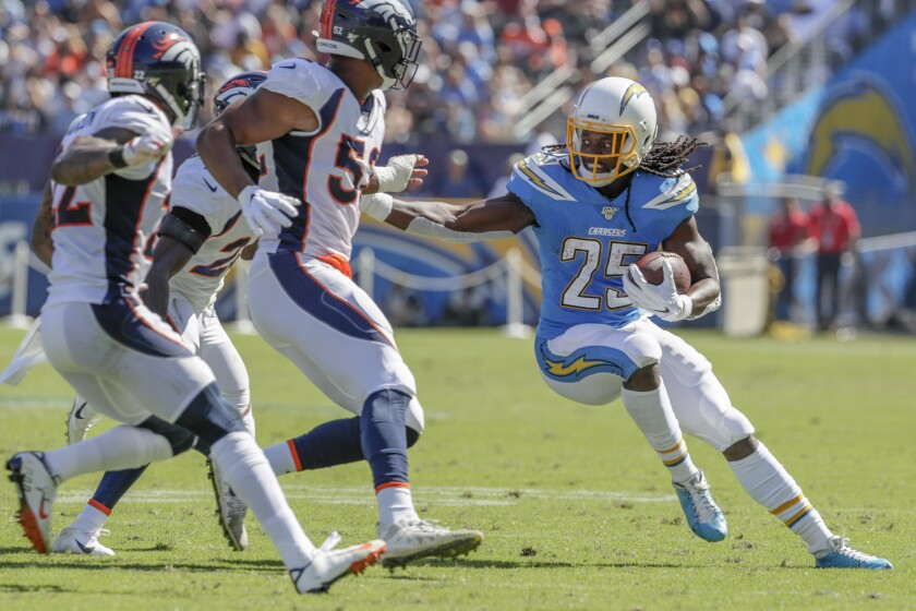 CARSON, CA, SUNDAY, OCTOBER 6, 2019 - Los Angeles Chargers running back Melvin Gordon (25) tries to avoid Broncos defenders during a first half run at Dignity Health Sports Park. (Robert Gauthier/Los Angeles Times)