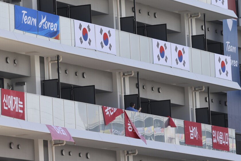 """Banners with the words """"I still have the support of 50 million Korean people,"""" are removed from balconies at the the Olympic athletes' village in Tokyo Saturday, July 17, 2021. South Korea's Olympic Committee said Saturday it has removed banners at the Olympic athletes' village in Tokyo that called up a 16th-century war between Korea and Japan after the International Olympic Committee ruled it was provocative. (Jin Sung-chul/Yonhap via AP)"""