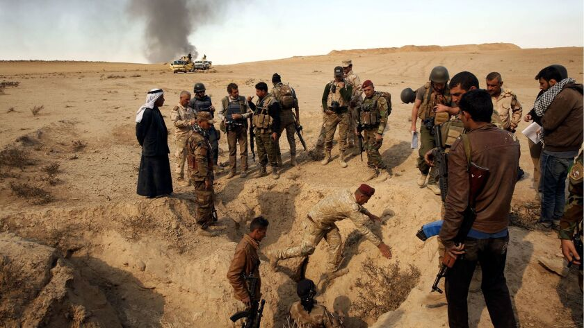 On the outskirts of the village of Hud, Iraqi soldiers visit a site where locals say Islamic State executed four or five people. Another gravesite containing many more people was in the area but soldiers said it was  too dangerous to visit due to mines.