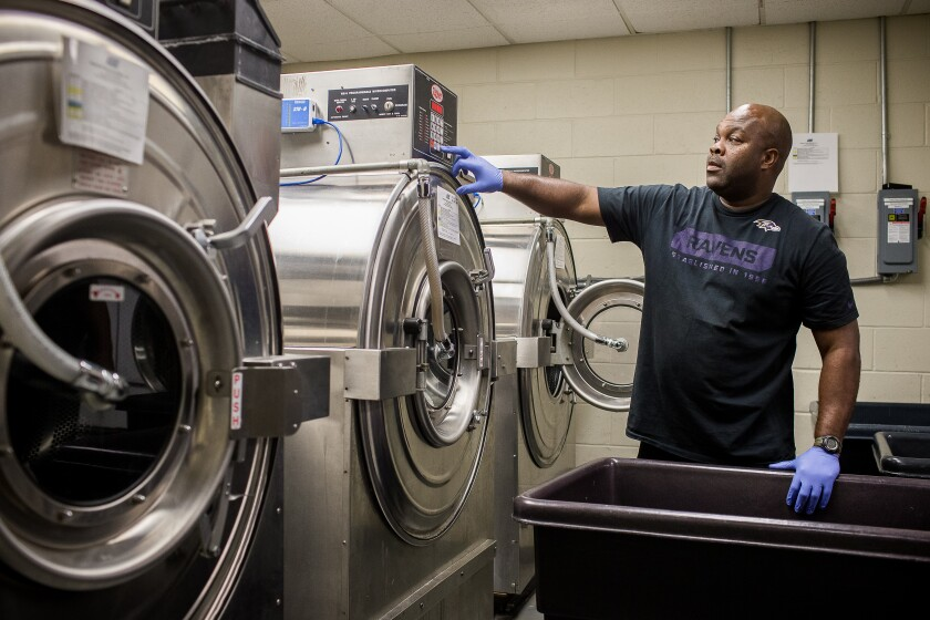 Fireman Avon Bryant, who works as a volunteer for the Baltimore Ravens, gets ready to unload a team washing machine.