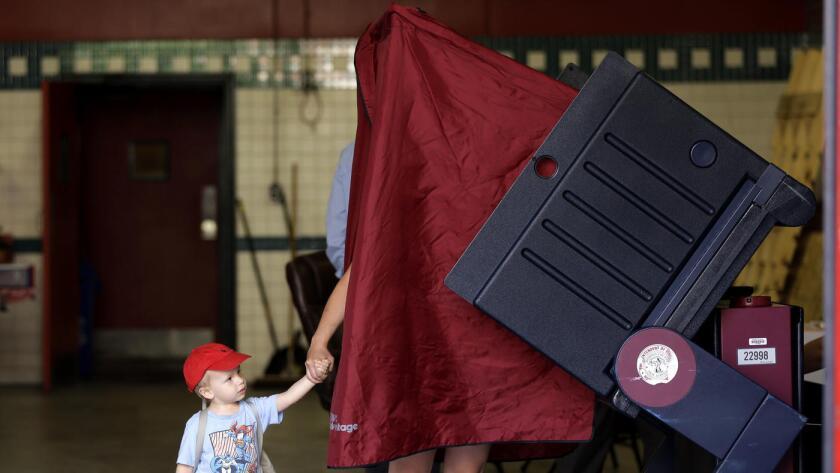 James Percella, de 2 años de edad, toma la mano de su madre mientras ella ingresa a una cabina de votación, en Hoboken, Nueva Jersey, el 7 de junio pasado.