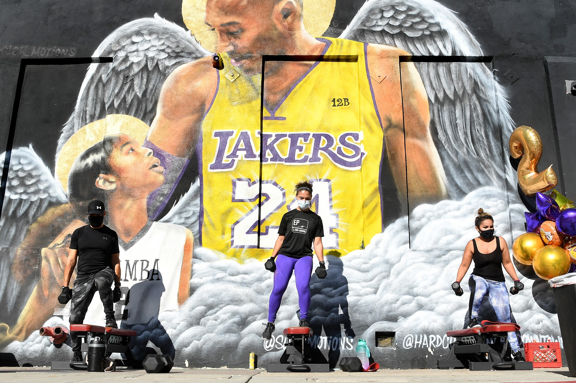 Three people hold dumbbells in front of a mural depicting Kobe and Gianna Bryant with angel wings.