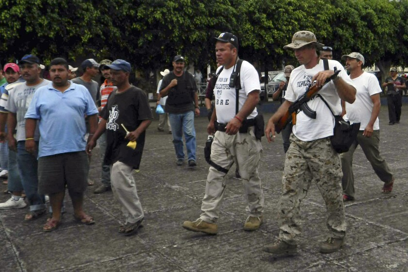"""Vigilantes arrive in the town of Pareo, in Mexico's Michoacan state. The Knights Templar drug cartel controls parts of the state, and a """"self-defense"""" movement has arisen to fight it."""