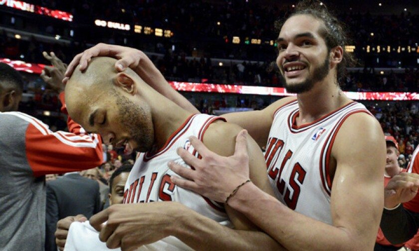 Taj Gibson is congratulated by Bulls teammate Joakim Noah after hitting a winning shot in overtime to defeat the Lakers, 102-100, on Jan. 20, 2014.