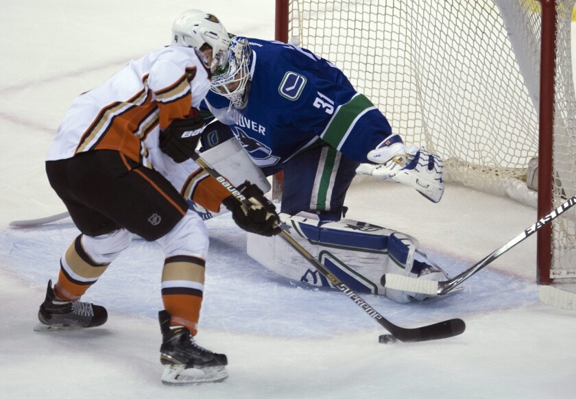 Defenseman Cam Fowler tries to shoot past Canucks goalie Eddie Lack during the first period of a game Monday in Vancouver. The Ducks lost to the Canucks, 2-1.