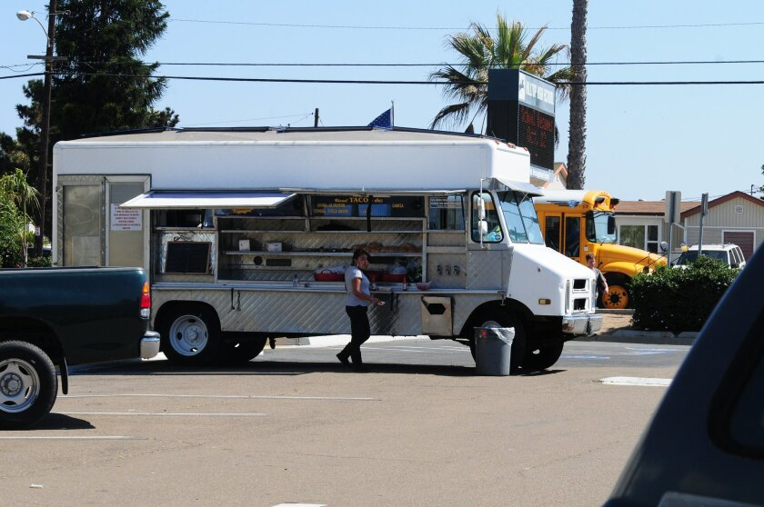 An approved food truck vendor solicits student business in the Hilltop High School parking lot. District officials say the vendors are only contracted to be on campus for specific after-school events.