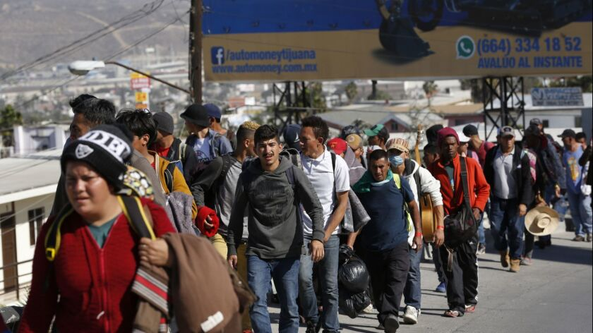Central American migrant caravan arrived in Tijuana by bus and after a brief stop for a meal left walking for La Playa.