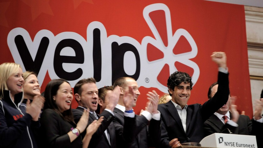 Yelp co-founder and CEO Jeremy Stoppelman (with fist raised) rings the opening bell during the company's March 2012 initial public offering. Is its business model under threat because of a California personal injury case?