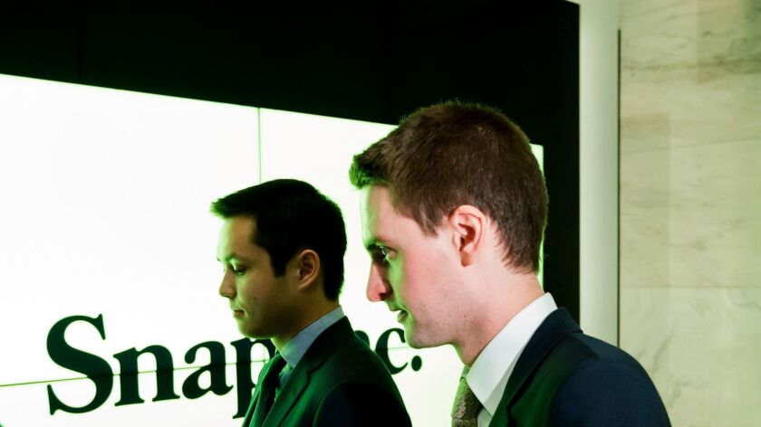 Snapchat co-founders Bobby Murphy, left, and Evan Spiegel stand together before shares of Snap Inc., the parent company of Snapchat, begin trading at the New York Stock Exchange.