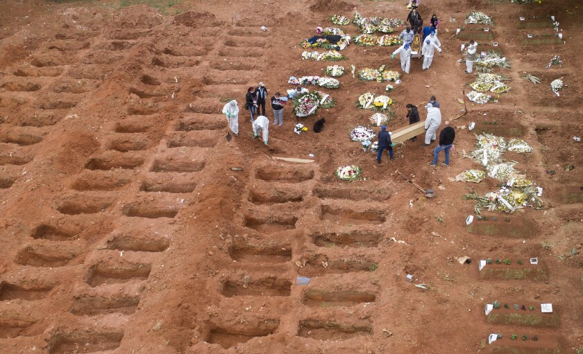 Cemetery workers in protective clothing bury three victims