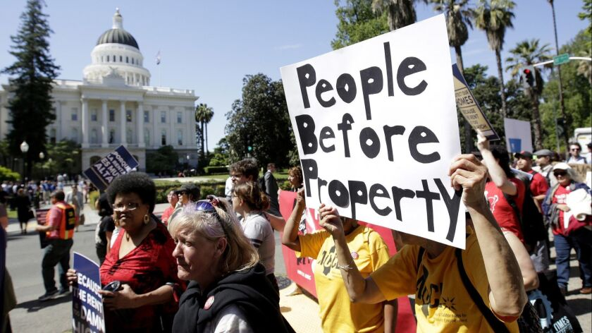 Supporters of a rent control initiative march near the Capitol calling for more rent control, Monday