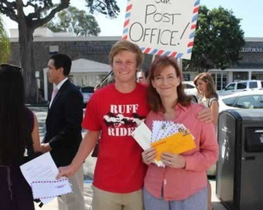 Thomas Wheeler joins Leslie Davis, chair of the Save Our La Jolla Post Office Task Force, during a letter-writing event Aug. 17 in front of the Wall Street post office. PAT SHERMAN