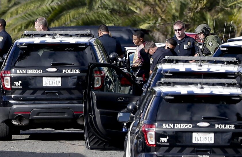 A suspect in a shooting, center, identified by police as Titus Colbert, is escorted away from an apartment building after an hours-long standoff with officials Wednesday, Nov. 4, 2015, in San Diego. Flights to the San Diego International Airport resumed after police took the gunman, who fired shots