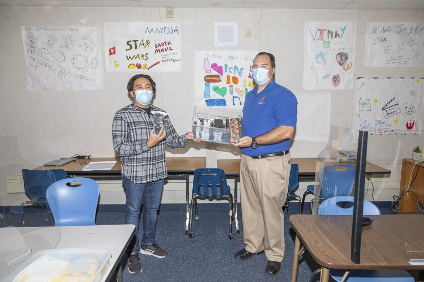 EUHSD special ed teacher Joseph Dionisio accepts 40 sets of earbuds from Jesse Middleton, Consuelo #325 Masonic Lodge.