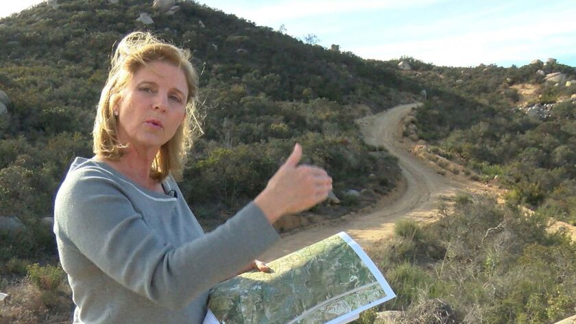 E Rita Brandin, Sr. VP ad Development Director for Newline Sierra, with a map near the high point of the property west of Interstate 15 and north of Deer Springs Road.