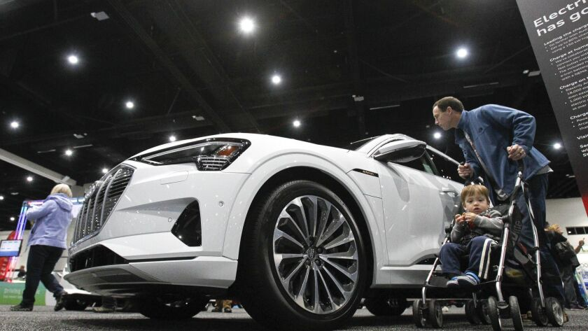 K.J. Hippensteel, from Carlsbad, his son J.J., look at the Audi e-tron electric car at the Eco-Center section of the San Diego International Auto Show at the San Diego Convention Center in San Diego on Saturday.