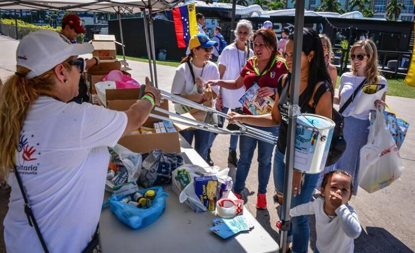 Un grupo de voluntarios recogen donaciones para Venezuela este sábado en una mesa instalada en el Bay Front Park, en Miami (Estados Unidos). EFE