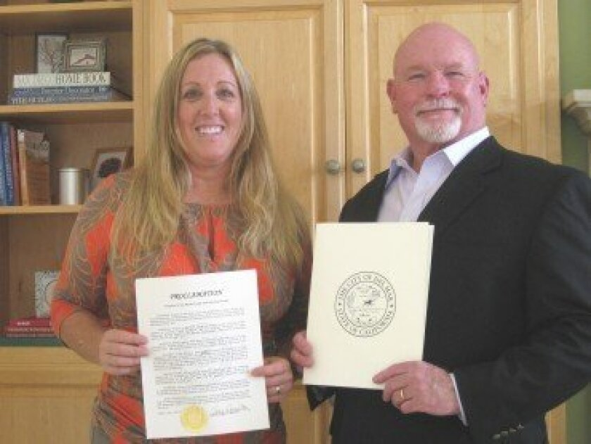 Development staff Shelly Dew and Don Beaumarchais display the City of Del Mar's proclamation at the Hospice of the North Coast's Pacifica House, where it will be placed.