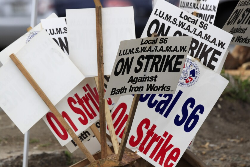 Striker's signs are gathered near Bath Iron Works, Wednesday, July 22, 2020, in Bath, Maine. The International Association of Machinists and Aerospace Workers Local S6 is in its fifth week of the strike over a new contract. The shipbuilder and union remain at odds over issues of seniority and subcontractors. (AP Photo/Robert F. Bukaty)
