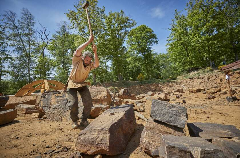 GUEDELON CASTLE, FRANCE - MAY 23: Alexandre Hecker, head quarryman, breaks a stone in the quarry at