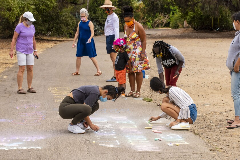 Participants in a Labor Day chalk-in draw on the La Jolla Bike Path in a show of support for the Black Lives Matter movement.
