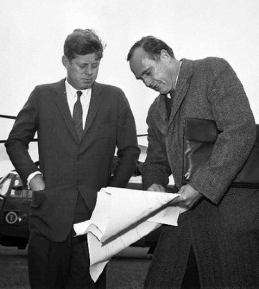 President Kennedy discusses drawings with architect John Warnecke as they look over a possible site for a library to house his public papers near Harvard University in Cambridge, Mass.