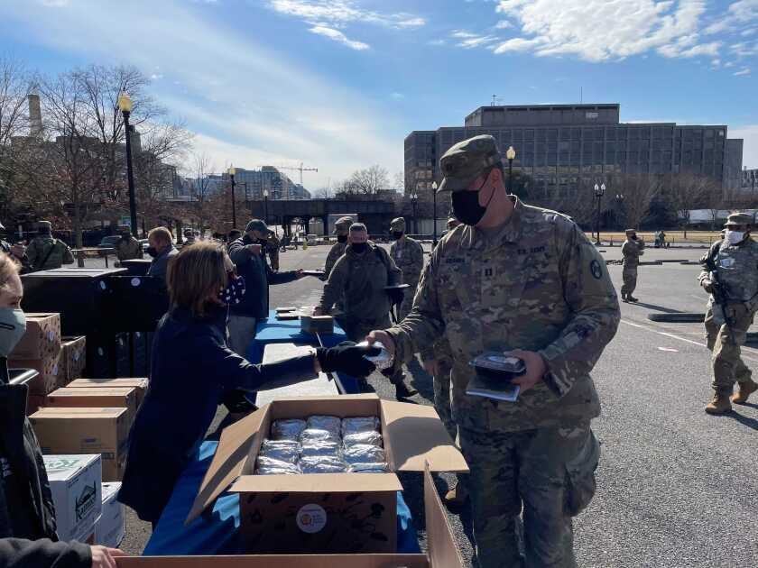 House Speaker Nancy Pelosi stands at a table with a box of packaged meals outside the Capitol.