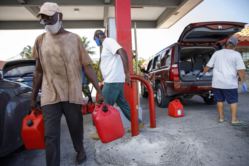 A resident walks with containers filled with gasoline at Cooper's gas station before the arrival of Hurricane Isaias.