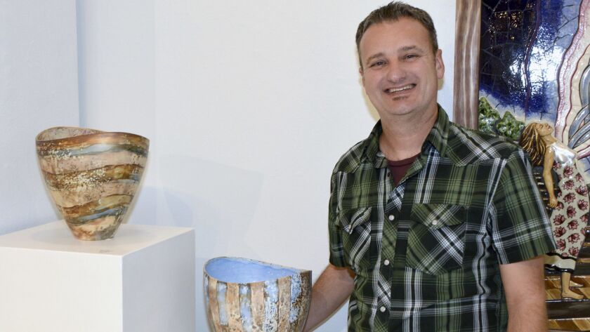 French artist Pierre Bounaud, who works in porcelain, showing off two of the 10 pieces he is current