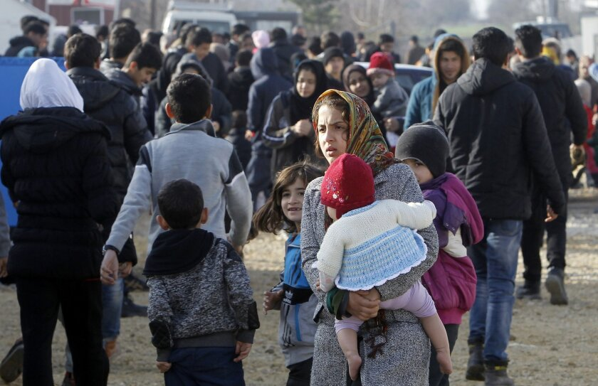 Refugees and migrants, mostly from Afghanistan, walk through the transit center for refugees near northern Macedonian village of Tabanovce, while waiting for a permission to cross the border into Serbia, Tuesday, Feb. 23, 2016. Hundreds of Afghan refugees were stranded since Saturday at the transit center in Tabanovce in northern Macedonia. Serbia says the decision to block refugees from Afghanistan from passing through the so-called Balkan migrant corridor has been made by Austria and Slovenia. (AP Photo/Boris Grdanoski)